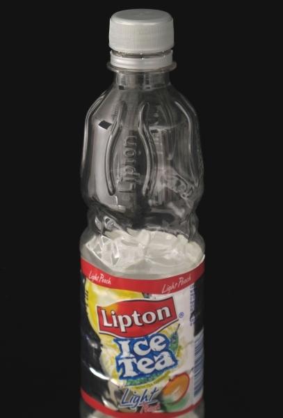 Flaske i klar plast med grå plastkork, etikett i mange farger av plastpapir. Engangsflaske. Varedeklarasjonsfelt med opplysninger om næringsinnhold og oppbevaring, varemerke og strekkode.