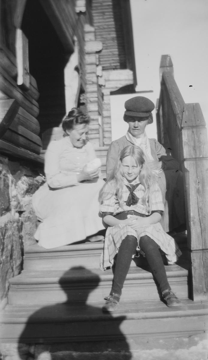 To damer og en jente sitter på en trapp av tre. Sola skinner.