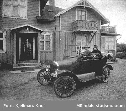 Lindome 1914-. Handlare Karl Andersson sitter i en T-Ford och hustrun sitter i baksätet. På trappan, i huset bakom bilen, står en kvinna och en hund.