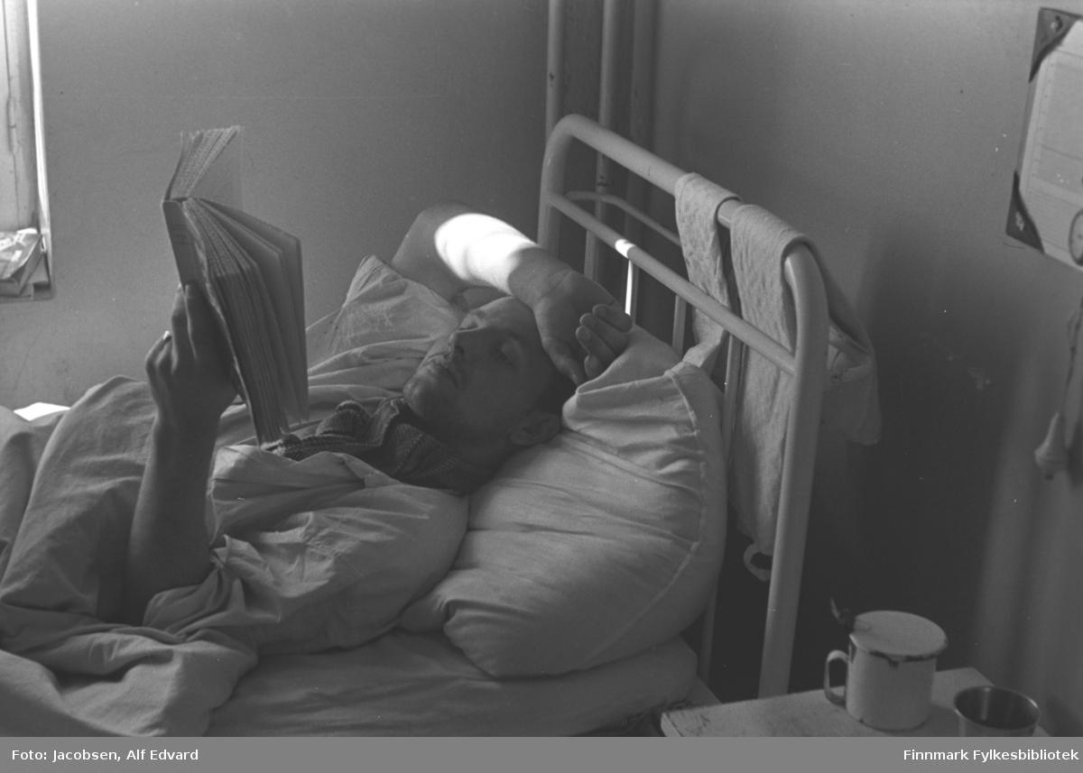 En mann ligger i senga si på St. Vincents Hospital. Han ligger på rygg og har høyre armen over hodet. Der kan man også se merke av litt solskinn. I venstre hånd holder han en bok. En bred ring ses på venstre ringfinger. Senga han ligger i har hvitlakkert metallramme og to lyse håndklær henger over gavlen. Sengeklærne er også hvit/lys. I halsen har han noe stripet tøy, muligens et tørkle eller skjerf. Den kortermede skjorta han har på er hvit/lys. Ved siden av senga står et hvitt nattbord. Oppå står et lyst krys med en teskje oppi og et glass/beger av metall. Veggene er lyse og ensfarget og enden av en snor ses oppe til høyre. Over den henger et papir med tekst og et rundt stempel, muligens informasjon. I hjørnet ses to vannrør, kanskje til et sentralvarmeanlegg. Helt til venstre på bildet er kanten på et vindu med noe liggende i vinduskarmen.