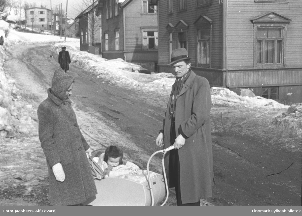Aase og Fridtjof Jacobsen med sønnen Arne fotografert i Tromsø. Aase har en ganske lys kåpe på seg med hvite votter og lue på hodet. Arne har en mørk dress på seg. Over har han en ganske lys frakk og hatt. Hatten er lys med en mørk stripe. Mellom dem står en lys barnevogn med kalesjen nede. Oppi sitter Arne Jacbosen. Han har en mørk lue på seg og et lyst teppe er pakket rundt han. Et stykke opp i gata går en mørkkledt person. Gaten der de står har et litt skittent snø- og islag. Det er noen snøkanter langs fortauene. Til høyre på bildet står et stort, ganske mørkt hus med liggende panelt. Huset har flere vinduer med mørke karmer på lang- og røstveggen. Trekantede vannbrett er montert rett over hvert vindu. Ved siden av er et stort hus til. Det er forholdsvis mørk-malt med mange vinduer på lang- og røstveggen. Flere hus ses oppover gaten, bl.a et lyst med 4 store vinduer på røstveggen. Noen trær ses i terrenget oppe til venstre på bildet.
