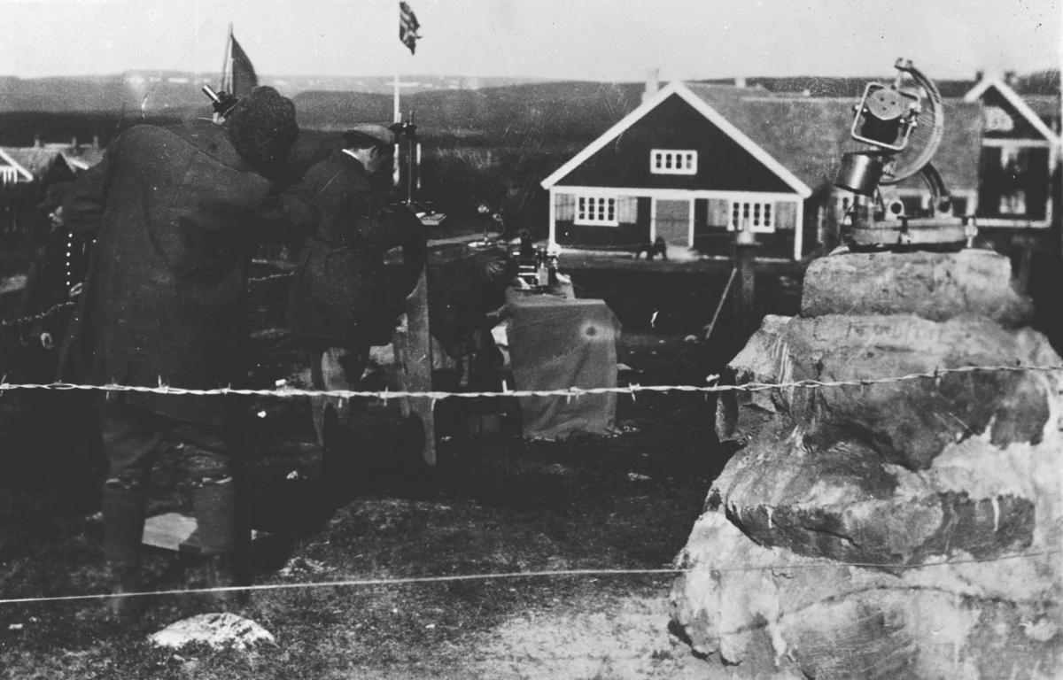 Solformørkelse i 29. juni 1927. Tre sivile menn med observasjonsutstyr i hagen på Nyborgmoen. Området der mennene jobber er omgjæret med piggtråd, (isolert som observasjonspunkt ?). Et observasjonsutsyr står opp på en steinraus på forgrunnen. Militærbyggninger på bakgrunn.