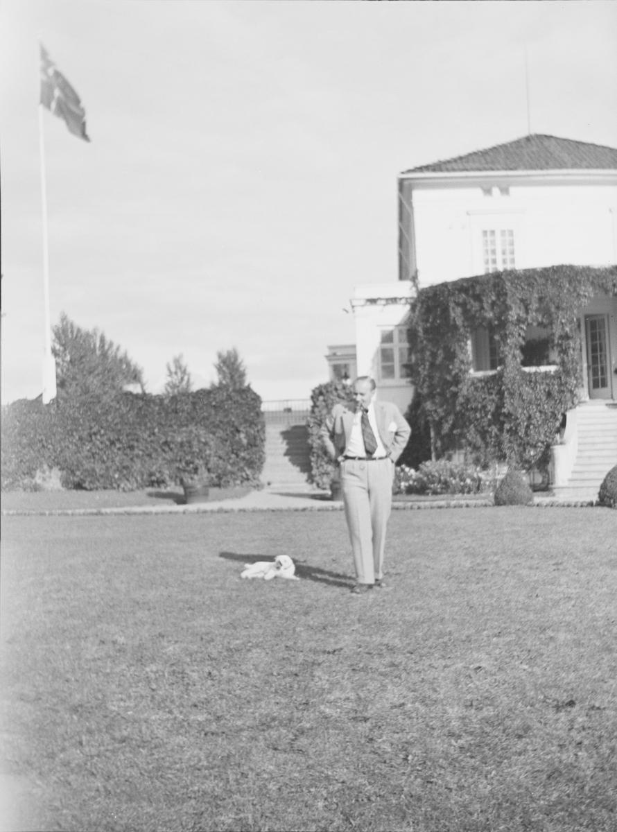 Iacob er fotografert på plenen i den victorianske hagen. En hund ligger rett ved ham. Flagget er heist.