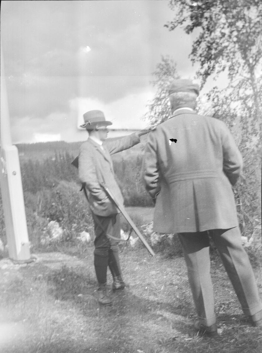 Far og sønn ser utover et skoglandskap. Kanskje er de i Jeppedalen? Faren, Christian Pierre Mathiesen, står med ryggen til og sønnen Haaken Christian Mathiesen peker mot skogen og har en hagle under armen. De står ved en flaggstang.