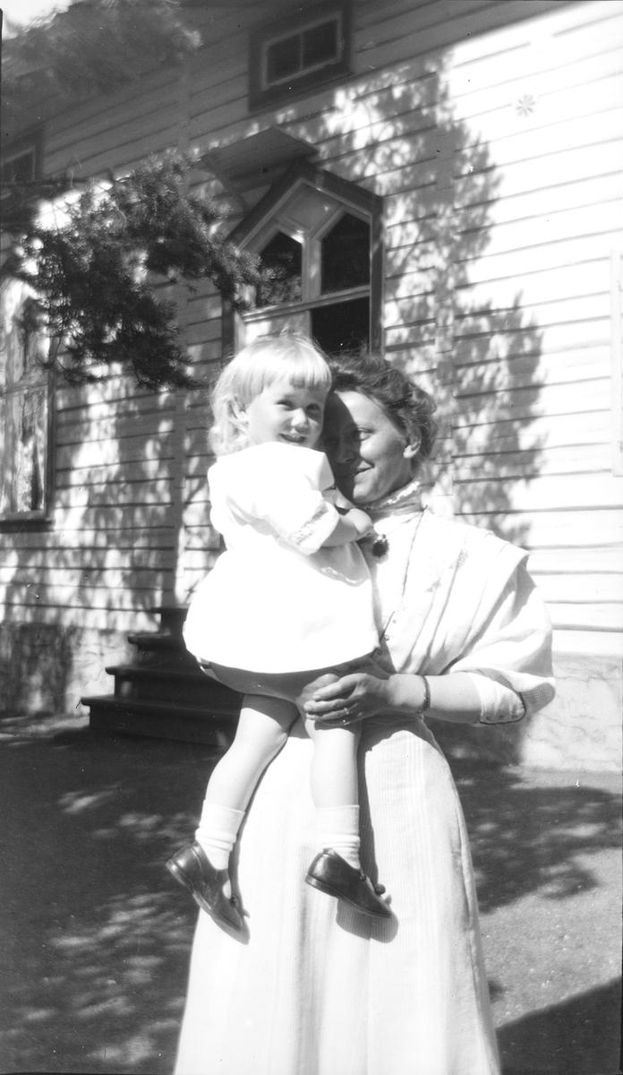 En kvinne med Iacob Ihlen Mathiesen på armen. I bakgrunnen sees et hus hvor furu vokser nært huset. Trærne skjærmer huset mot solen og lager fint mønster på veggen.