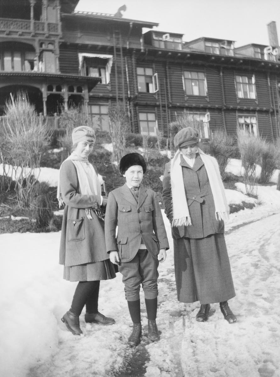 To unge kvinner og Iacob Ihlen Mathiesen står på en slapsete (snøslaps) vei som fører opp til inngangen på Holmenkollen Turisthotel.