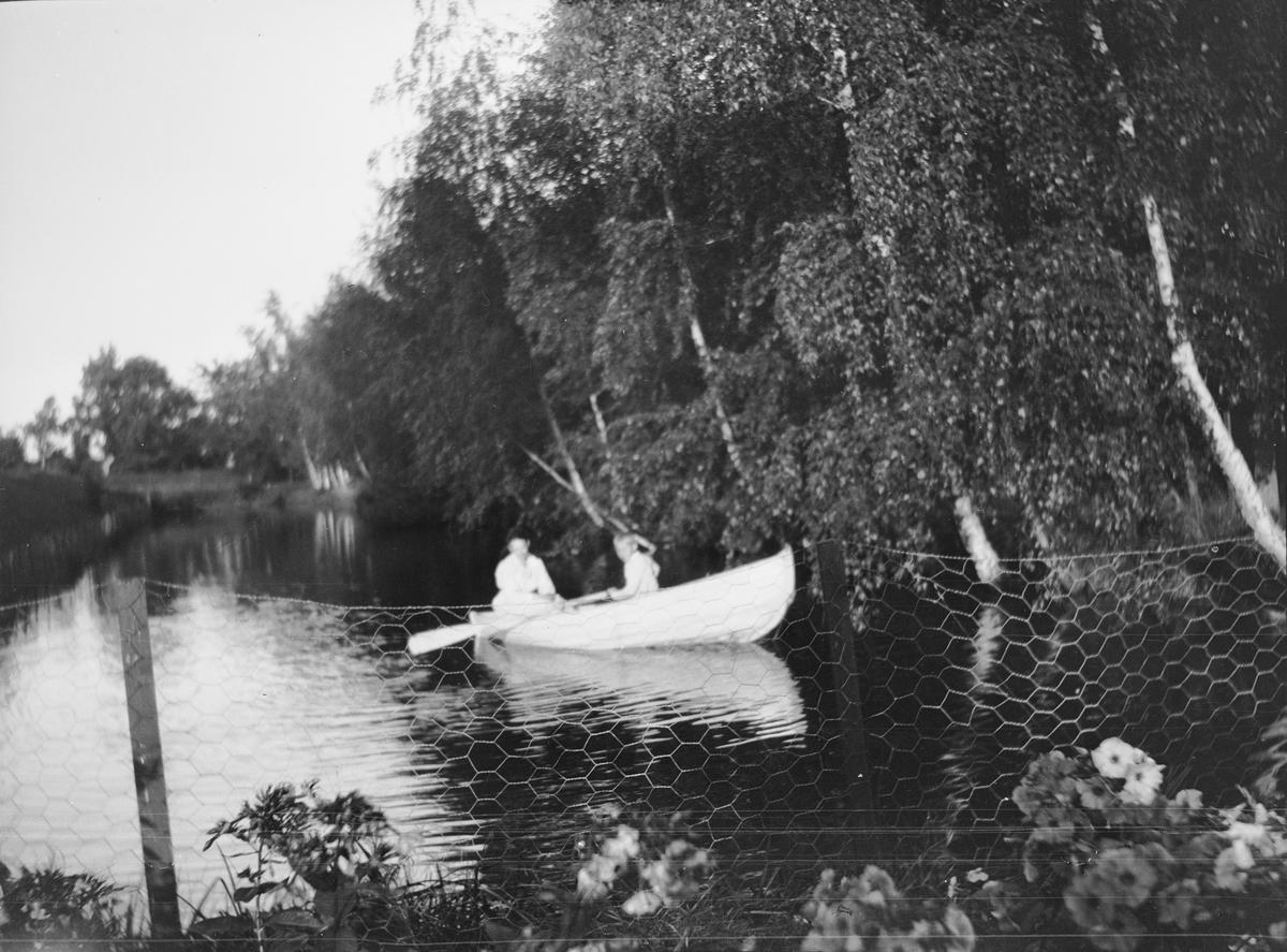 """En gutt er ute å ror på karpedammen også kalt """"kanalen"""". Dammen ligger nederst i terrassehagen på Linderud Gård og går langs med """"Lindehallen"""". En kvinne sitter bak i båten. Grener av bjørk henger ut over dammen. I forgrunnen sees et"""