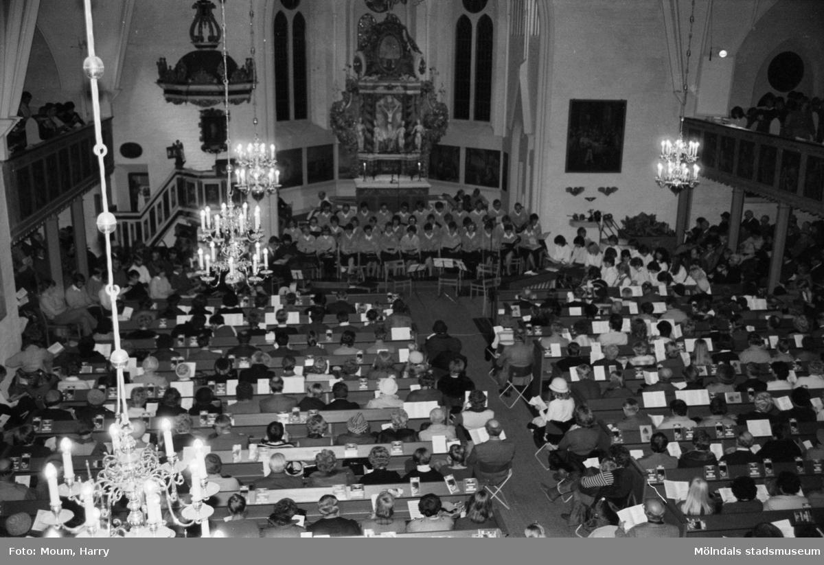 """Sju körer sjunger julsånger vid """"Julens sånger i centrum"""" i Fässbergs kyrka i Mölndal, år 1983.  För mer information om bilden se under tilläggsinformation."""