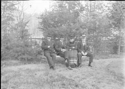 Gruppebilde på benk ute, en kvinne, tre menn
