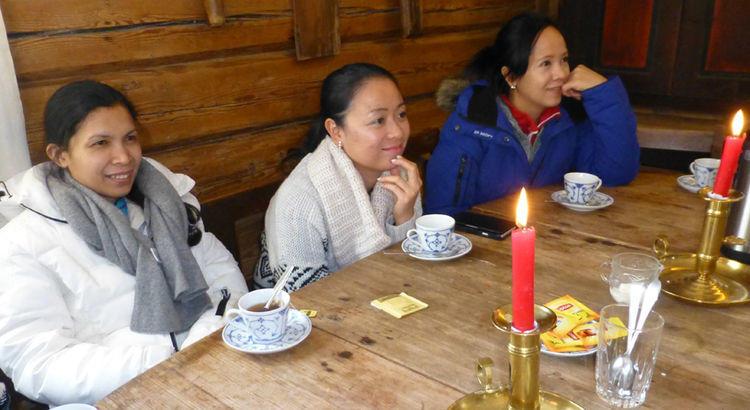 Tre damer fra Voksenopplæringen i Skedsmo sitter ved et bord og drikker te og hører eventyr.