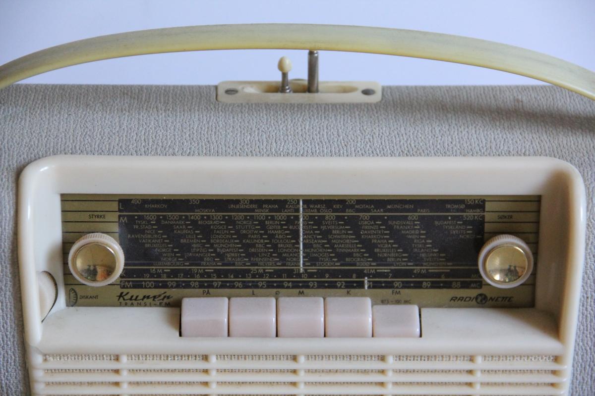 Stående modell, rektangulær med bred bunnplate og smalere topp-avslutning, Håndtak og to antenner på toppen. For elektrisk tilgang. Høytale rmed riflet flate i front. To knapper på frontpanel: søker og volum.   b) eske av tykk papp, original emballasje