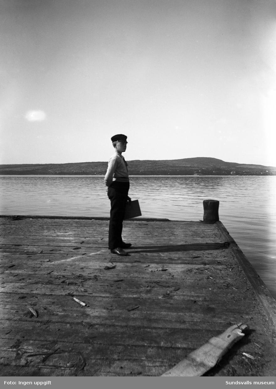 En pojke blickar ut från en båtbrygga. Troligen på Alnösidan eftersom man kan se över till Skönsmon och Villa Kumo på fastlandet i bakgrunden.