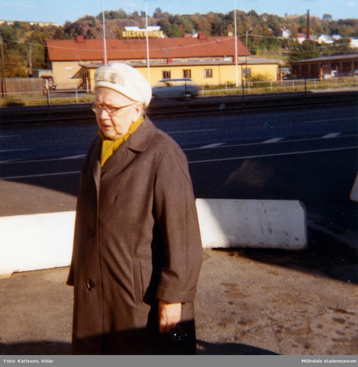 En glasögonprydd dam, klädd i brun kappa och vit hatt som står på Göteborgsvägen, år 1972. I bakgrunden syns spårvagnsspår, järnvägsspår och Ågatan.