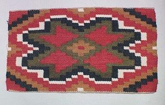 Vävprovet har oblekt lin i varpen. Mönster/inslag är av ull i färgerna röd, grön, blå, naturvit och gulbrun.