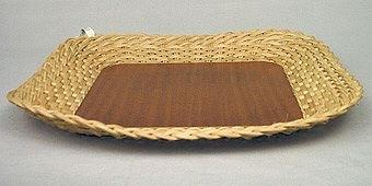 Korgfat flätat av runddragen och kluven rotting. Spröten är inborrade i sidan på en träfanérplatta som utgör botten.