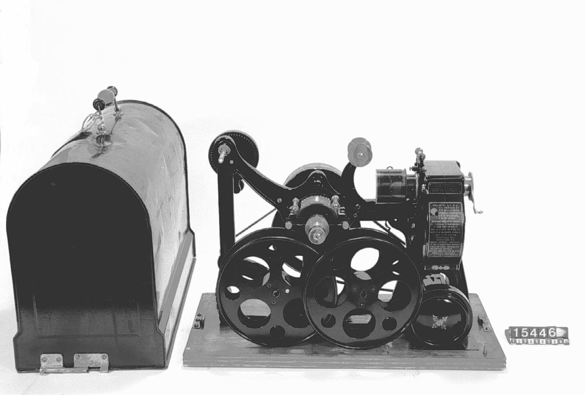 """Handdriven projektor för normalfilm """"Pathé Kok"""". Optik av okänd typ (främre linsen har oljestänk). Bländare: I projektorverket inbyggd rotationsbländare av plåt.  Spolarmarna är så korta, att endast specialspolar, rymmande en mindre mängd film, kan användas.  Frammatningsanordning: Från den bakom projektorverket liggande förrådsspolen dras filmen ned av ett centralt tandhjul, bildar en slinga och löper ned i filmbanan där den frammatas av en entandad dubbelgripare och bildar ännu en slinga, passerar det centrala tandhjulet samt spolas upp på den bakom verket placerade uppsamlingsspolen.  Något för denna apparat specifikt är, att de bakåt riktade tryckskenorna i filmbanan inte är plana, utan vågiga. Denna anordning innebär troligen en vinst på filmslitagets konto. Bildstrecksinställningen sker genom förskjutning av bildbegränsningsmasken. Tryckreglage i filmbanan.  Belysnin Tillbehör: Vev, huv och tre filmspolar."""