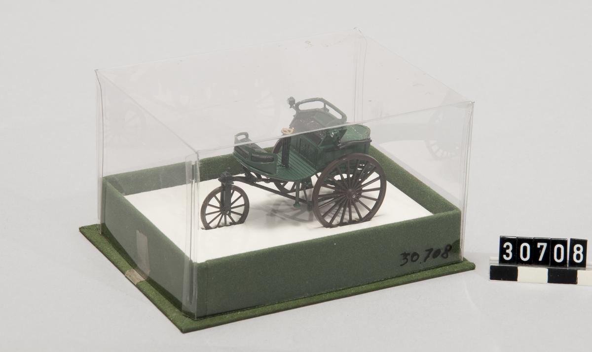 Modell av Benz trehjulsbil, gjuten i plast med hölje av plast. Till färgen grön med svarta hjul och säten. Märke: Benz. Tillverkningsår: 1880. Bilens längd: 70 mm, bredd: 34 mm, höjd: 37 mm, Höljets längd: 105 mm, bredd: 80 mm, höjd: 60 mm.