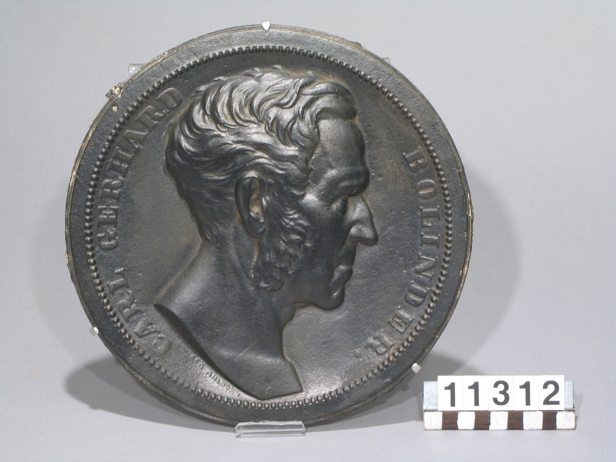 """Medaljong, av gjutjärn, Carl Gerhard Bolinder, höger profil, låg relief. Medaljong efter modell av Lea Ahlborn. """"Lea Ahlborn"""". """"Carl Gerhard Bolinder"""". """"J. & C. G. Bolinder, Stockholm""""."""