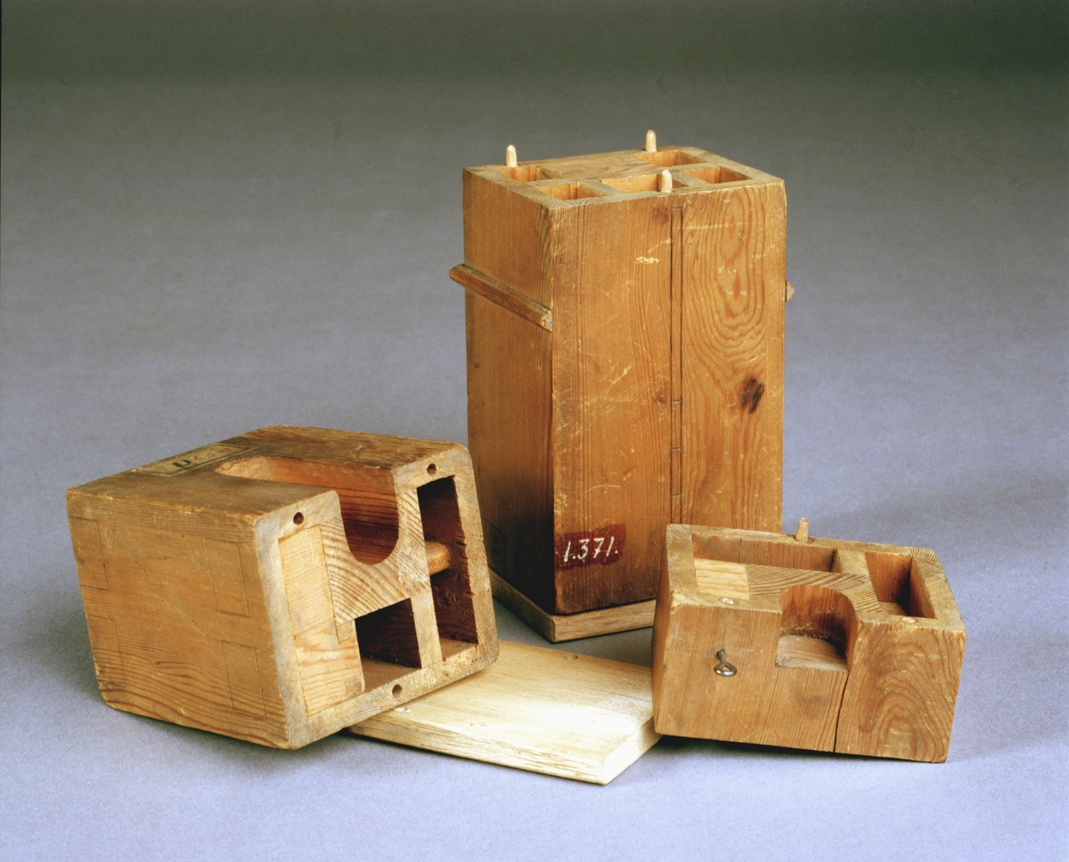 """Modell av kakelugn. Text på föremålet: D.b.B.4.c-"""". Två delar: krönet och fundamentet, saknades vid ankomsten till TM. I Jonas Norbergs förteckning från 1779 beskrivs modellen på följande sätt: """"Modell på Kakelugn med 4 rör utom eldstaden, samt dubbel ingång och med 2:ne spjäll."""""""