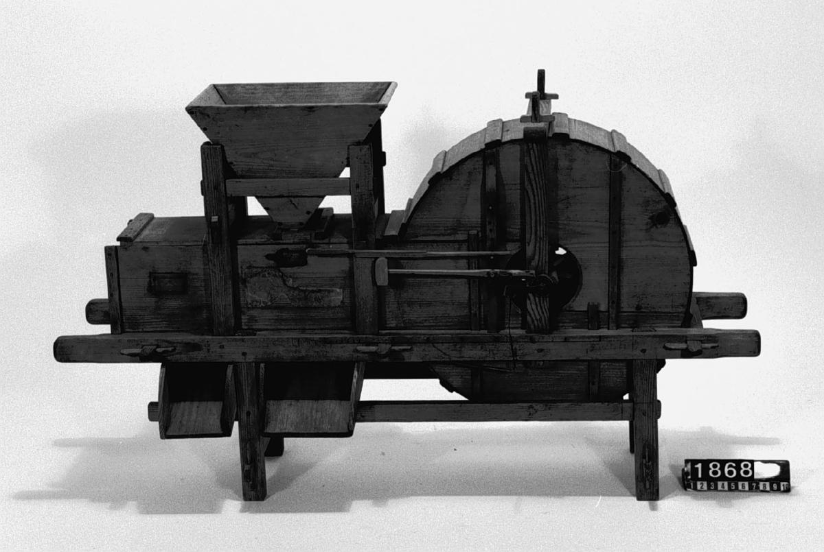 """Modell av sädesrensningsmaskin. Text på föremålet: """"N:o 110. Modell på .... kastnings-machin med ..... Förbättringar af Comissar. Norberg. F-b-26 N:o 75"""". I Jonas Norbergs förteckning från 1779 beskrivs modellen på följande sätt: """"Modell på kast Machine, at kasta den uttröskade sädes drossan, sedan den förut lupit genom et såll, hvaruti axvipporne stadna, gjord av undertecknad."""""""