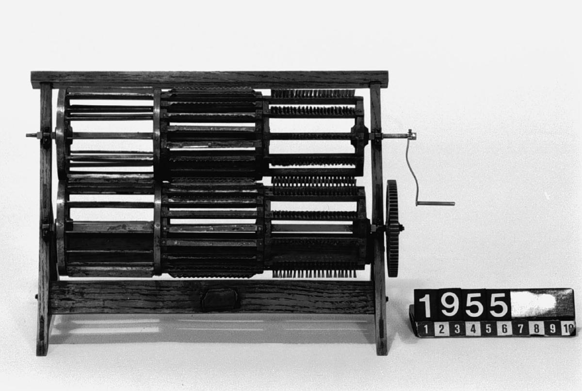 """Modell av inrättning för bråkning, skäktning och borstning av lin, av Schwartz. Text på föremålet: """"Maskin för bråkning, skäktning, häckling och borstning, av Svartz."""" på etikett,  och """"Wallström 18 11/6 36"""" med bläck. N:o 89."""