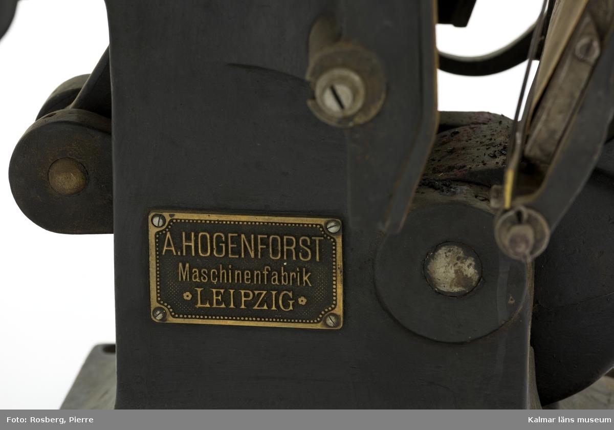 KLM 45374:38. Digelpress. Av metall. Liten digelpress av svartmålad metall, stommen av gjutjärn. På pressens ena gavel finns en metallskylt. På den står texten: A Hogenforst Maschinenfabrik Leipzig. På den andra gaveln finns präglat i gjutgodset texten Hogenforst samt vad som troligen är en logotype. Pressen är intakt med valsar. På digeln sitter ett tryck från JN Blomgrens tryckeri.