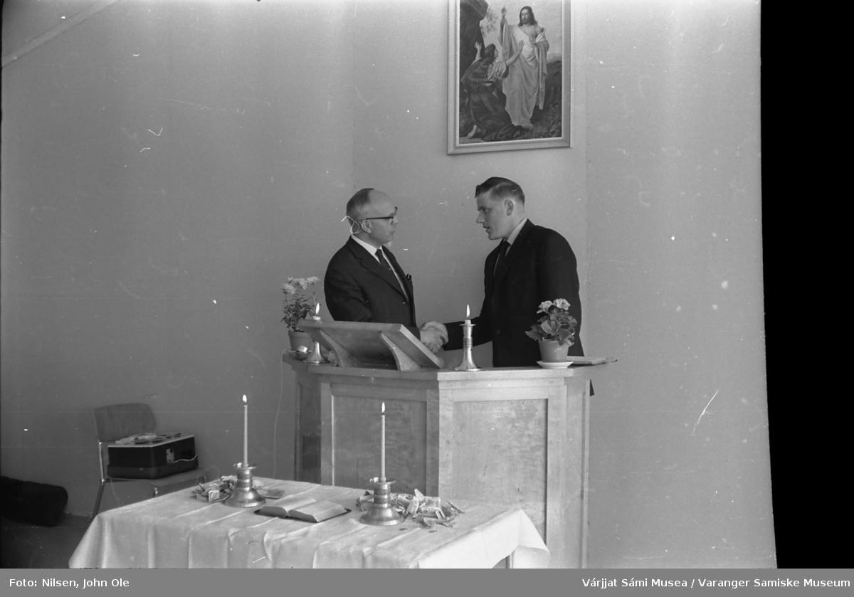 Innvielse av ungdomssenteret i Vestre Jakobselv. Steinar Harila står til høyre på tale / prekestolen og håndhilser på en mann i sort dress. På stolen til venstre ligger en båndopptaker. 19. juni 1966.