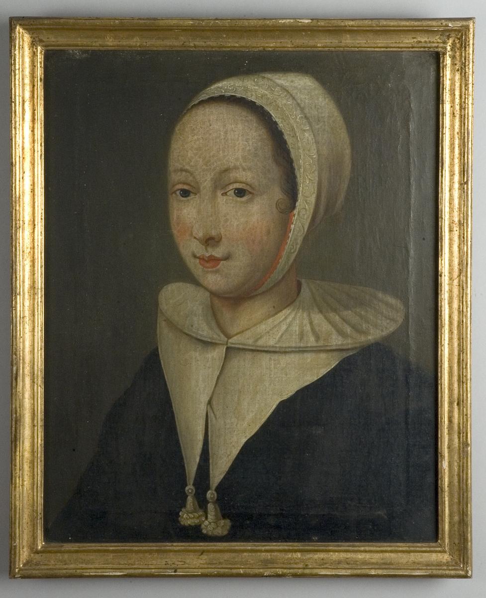 Bröstbild av kvinna i svart klänning med vit krage och vit mössa mot mörk bakgrund.