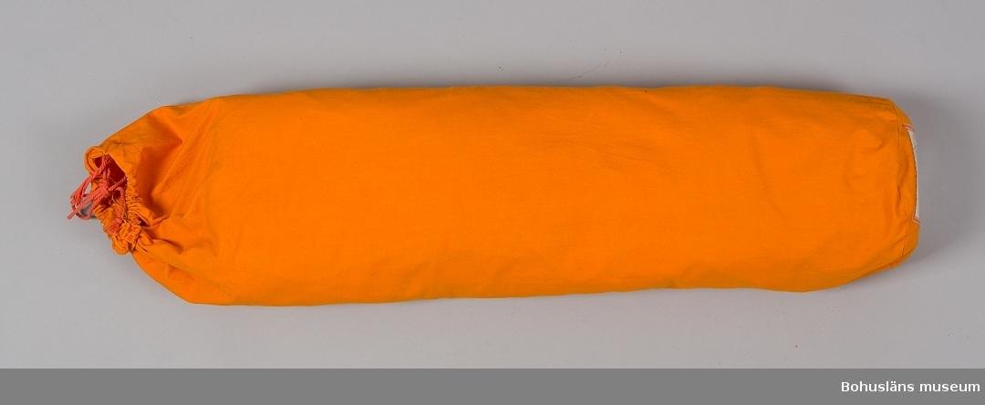 """Förgård av orange specialimpregnerad tältduk i bomull, modell 35198. Förgården sammanhör med stativtält modell Malaga de lux 35197, UM27670:1.  Till tältet hör också tältstänger UM27670:3, tältpinnar UM27670:4 samt vägledning för uppsättning och nedmontering UM27670:5.  Förgårdens mått är 240 x 120 cm och kopplas samman med tältet via dragkedjor.  Det sätts upp med tredelade tältstänger av stålrör med ändar av röd plast och tältpinnar av rundstål. Blixtlås i förkromad metall. Förgården är i ett enda stycke och kan stängas helt med dragkedjor och öppnas åt båda sidor samt har ett stort fönster av klarplast försett med gardin. Förgården är förpackad i en säck med dragskosnörning av samma orange tältduk, UM27670:2. I botten på säcken en plastficka med beskrivning av förgården OCH VDN VARUFAKTA samt RÅD VID TÄLTSLAGNING.   ABC-fabrikerna (Aktiebolaget Bröderna Claesson) hade en omfattande tillverkning av sport- och fritidsartiklar. Under en tid var de Nordeuropas största tillverkare. Mellan åren 1972 och 1982 fortsatte delar av verksamheten under företagsnamnen JOFA AB, VOLVO-fritid, ABC-verken, ABC-Reseffekt.  Insamlad i samband med egenproducerad utställning om ABC-fabrikerna, visad på Bohusläns museum 13 maj - 30 september 2001. Utställningen visades på Kungälvs bibliotek senare samma år. Från ABC-fabrikernas produktion insamlades följande material från olika givare: UM27670 - UM27700, UM27725 - UM27735, UMFA54418 Se Bilagepärmen UM27670 med kopior på tidningsartiklar.  Litteratur: ABC-boken nr 82. Huvudkatalog sommaren 1956. Göteborg 1956.  Berg, Kerstin, Berg, Harry: Kungälv - en stads historia.  s. 136 - 140. 1992. Nordström, Thure: """"...att jobba te Claessons. En bok om ABC-fabrikerna."""" Kungälv 1990. Johansson, Sigurd, Berg, Kerstin, Berg, Harry: Det gamla Kungälv, s. 129 - 135. 1986."""