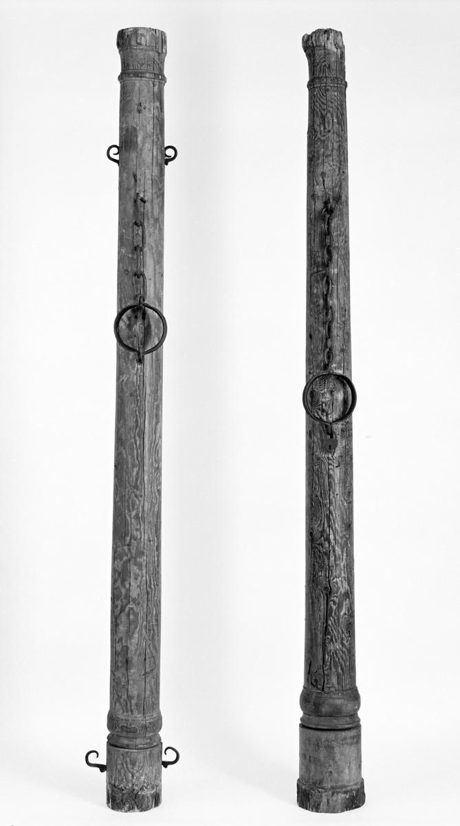 To brune trestokker med enkel utskåret profilering i form av runde bånd øverst og nedert. Begge stokkene har halsjern med lenke. Halsringen på stokk b har hengelåsen intakt. Stokk a har fire jernbøyler stikkende ut på sidene, to oppe og to nede.