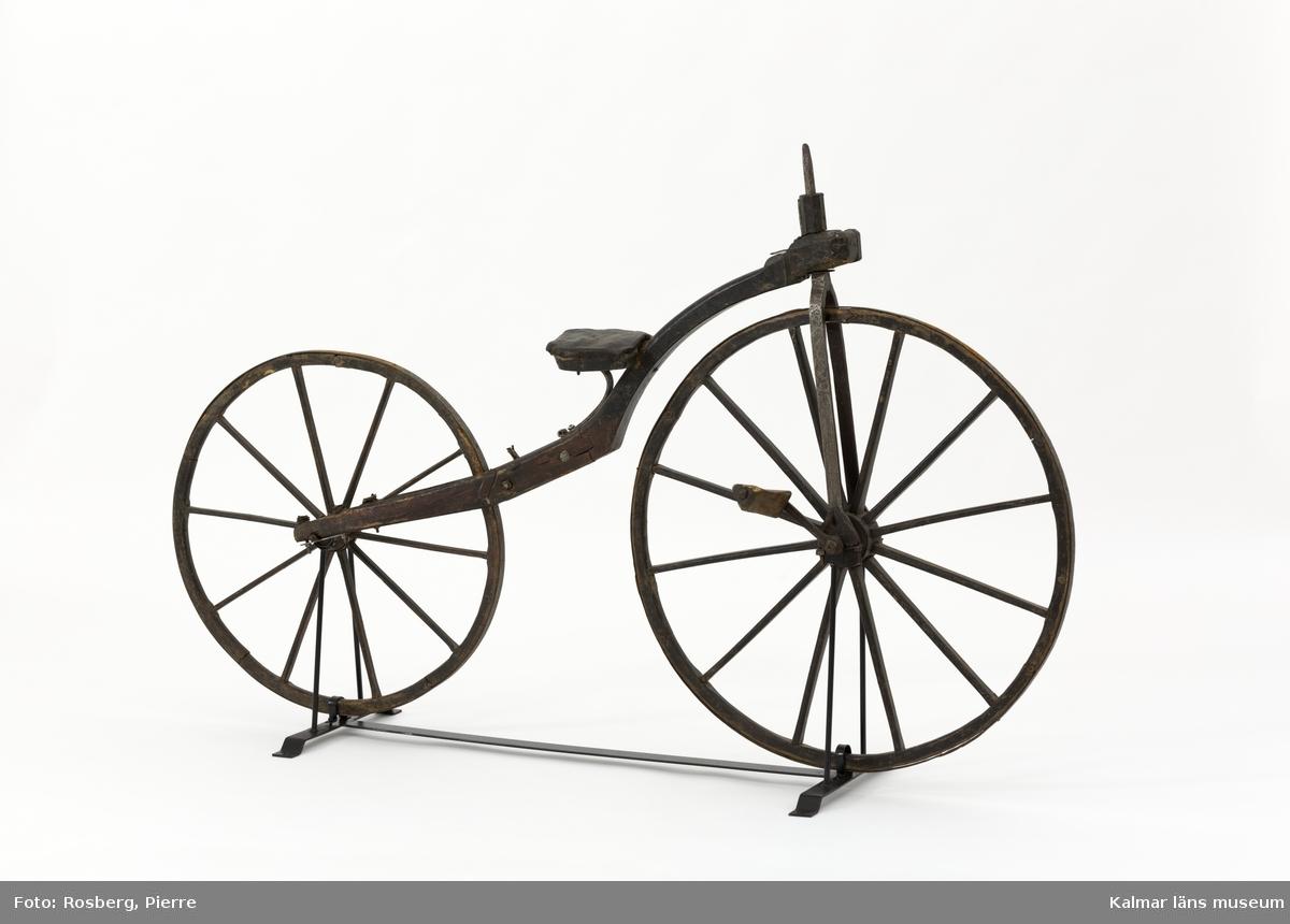 KLM 9610. Velociped, benskakare. Av trä och järn. Hjul och ram av svartmålat trä, ramen har spår av röd färg. Hjulen är järnskodda. Framgaffel och mindre detaljer av järn. Trampa av trä. Framhjulet, med 12 ekrar, är större än det bakre med 10 ekrar. Läderklädd sadel. Styret och ena trampan saknas. Hemgjord.