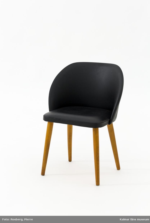 KLM 45619:18. Stol, sminkstol. Mindre stol med svart konstläder rundat ryggstöd och sits. Ben av trä. Lapp under sits: S a.b slätte möbler.