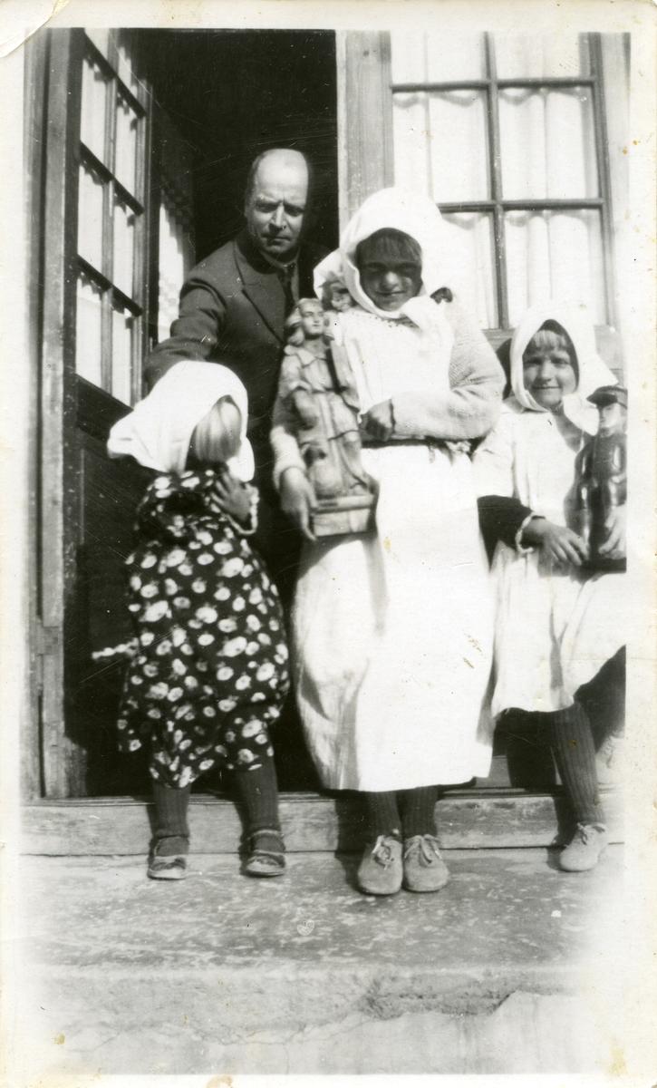 Tre små jenter står på en trapp foran en dør. Jentene har alle tørkle på hodet. To av dem holder en figur i hendene. Bak dem står det en mann.