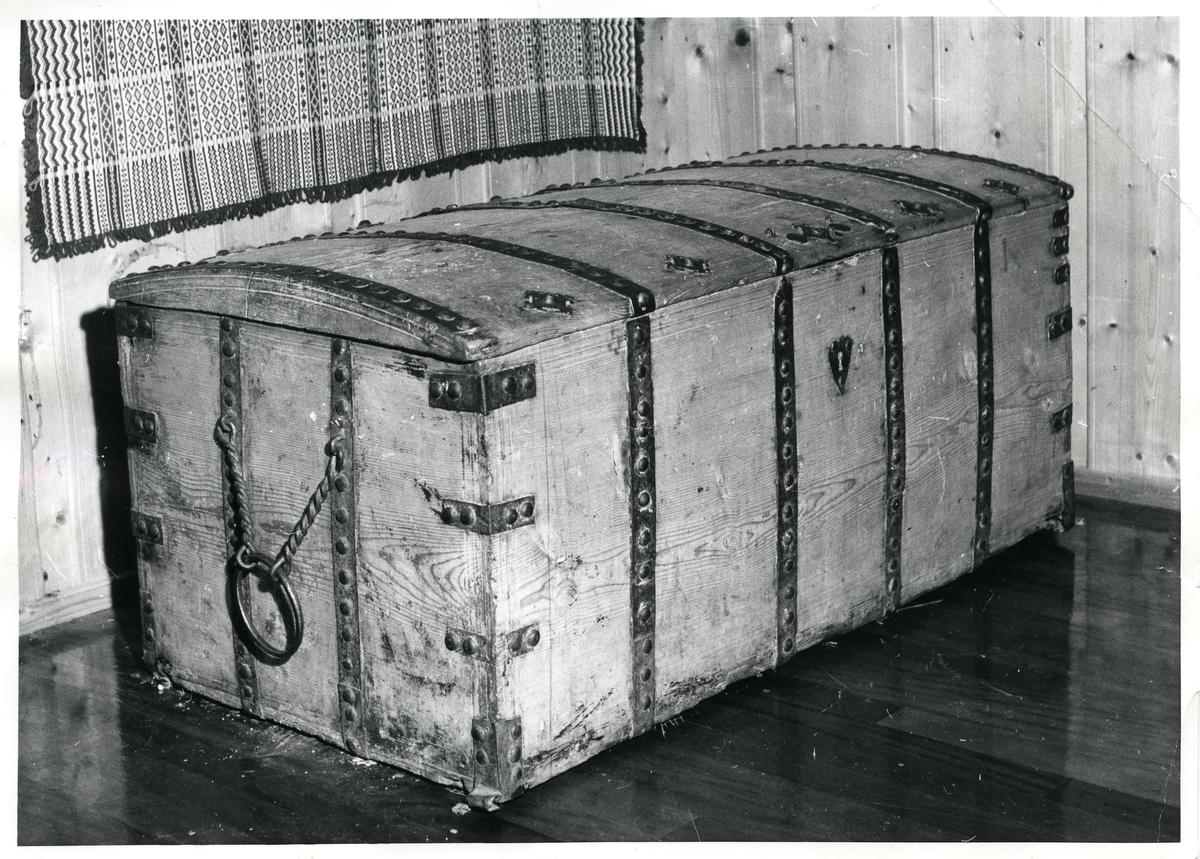 Stor trekiste. Kisten har metallbeslag på seg og en stor bærehank på siden.