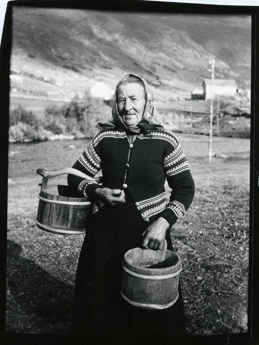 Portrett av kvinne iført skaut og lusekofte. I hendene holder hun noen trespann, såkalte mjølkeringje og kalvask fra Elvheim i Øye i Vang kommune.