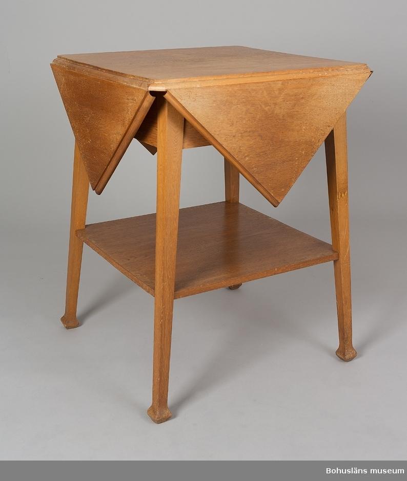 Fyrsidigt bord med fyra tresidiga klaffar. Hylla under. Nedåt divergerade ben.