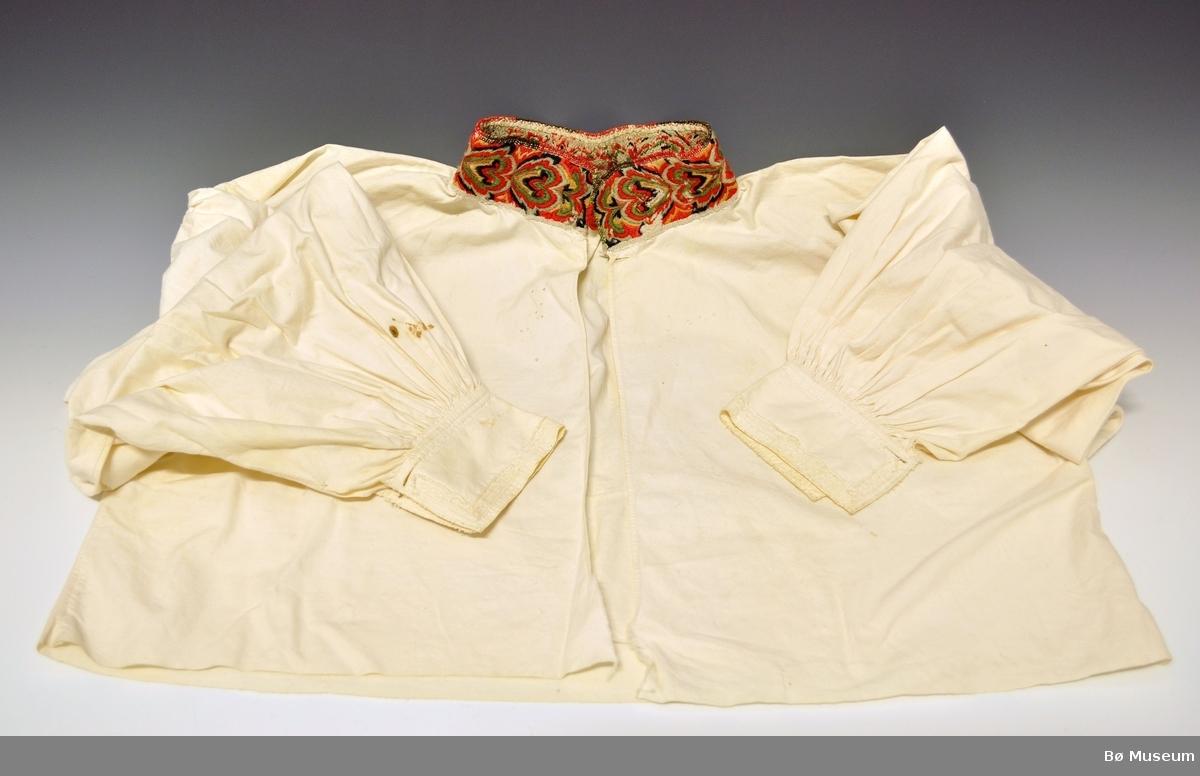 Skjorten har vid fasong uten skuldersømmer, men sidesømmer. Ermene er rynket oppe og nede, det er påsatt ermlinninger som er dekorert med smale blonder i ytterkant, og det er  1 knapphull på hver side. Åpningen framme er åpen helt ned, det er sydd et knapphull øverst oppe under halslinningen.  I halsen er det sydd på en halslinning som er brodert i plattsøm med ullgarn. Halslinningen har en hempe i ullgarn på den ene enden, samt broderte tagger øverst mot halsen. Det kan se ut til at halslinningen kan ha tilhørt en annen skjorte tidligere.  På baksiden av halslinningen er det brodert inn H G S (B)? 1811.