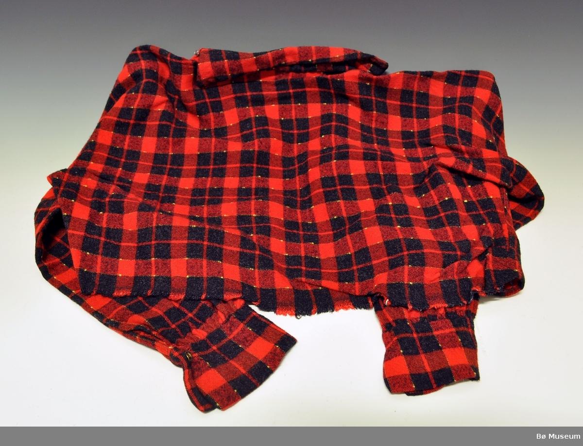Skjorte med krave og brystduk, i rødt og svart rutemønster. Skjorten er sydd i et stykke tøy, det er klippt ut til ermer i hovedtøyet.