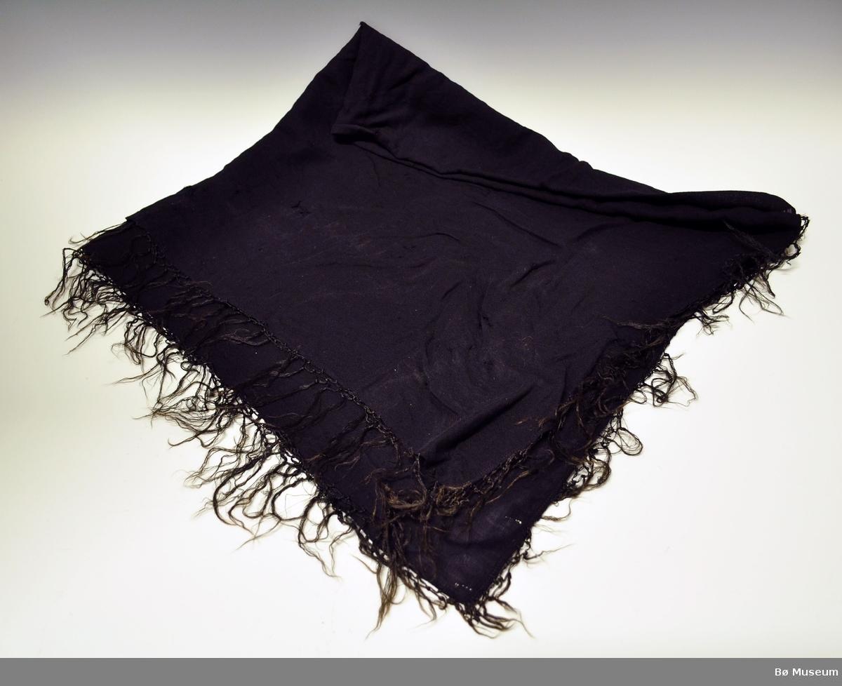Kvadratiske svart sjal i ull.Brukt til stakk og liv. Sjalet har smal  fald i to av sidene og jarekant i de to andre sidene. Sjalet har frynser i kunstsilke på alle fire sidene. Sjalet er i vevd i tynt ullgarn, kypertbinding. Mange hull og rifter etter møll.