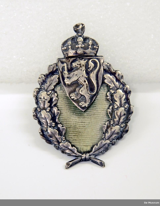 """Pin - """"emblem"""" uten noen påskrift eller innskrift: I sølv, formet som en laurbærkrans - med Den Norske Løve og krone på toppen. Nål på baksiden. Ribbeband (av samme type som blir brukt til medaljebånd) fyller midten av laurbærkransen  limt på på baksiden. Dette stoffet er lysegrønt - antagelig svært falmet."""