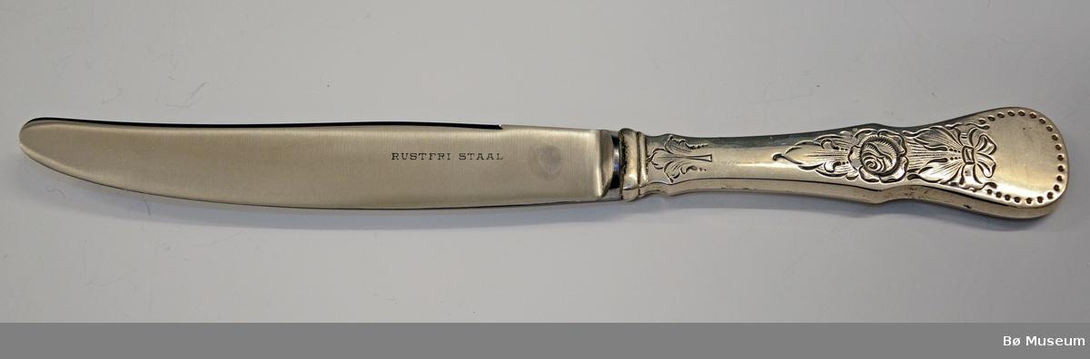 Kniv, sølv. Hører sammen med gaffel BØB.2015:0156.   Stempel: 830 S ) (= merke til Thorvald Marthinsen, Tønsberg). På bladet (På motsatt side av der stempelet står): RUSTFRI STAAL. Mønster: Rose