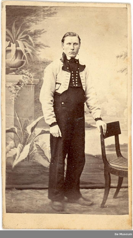 Yngre mann, fotograf Halvor H. Skogen, i gråkufte/langbukse ståande i atelier.