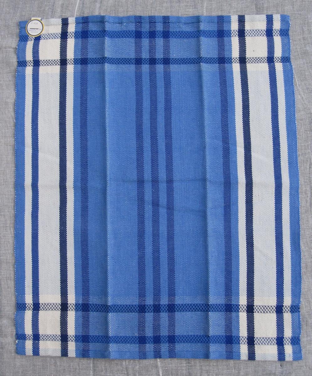 Randig handduk i flera blå nyanser och vitt, 8 mm smal fåll.  Handvävd blå hank.  Märkt med en gul och blå pappersetikett från  Svenska Hemslöjdsföreningarnas Riksförbund.