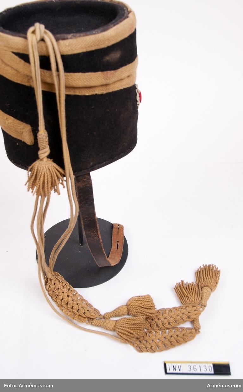 Grupp C I. Tillbehör till mössa. Ur uniform för manskap vid Skånska husarregementet; 1816. Består av dolma, päls, byxor, mössa, plym, tillbehör, halsduk, handskar, skärp, stövlar, sporrar, kartusch med rem, sabelkoppel, taska med remmar, sabelhandrem.