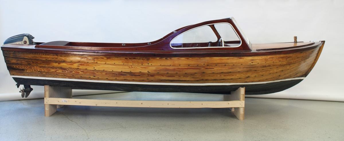 16 fots Tunejolle med dekk og vindskjerm. 9 bordganger. 2 rom(?) Dette eksemplaret har fordekk, vindskjerm og kalesje. Klinkbygd med spant - furu, mahogny. Avbildet påhenger tilhører ikke båten opprinnelig.