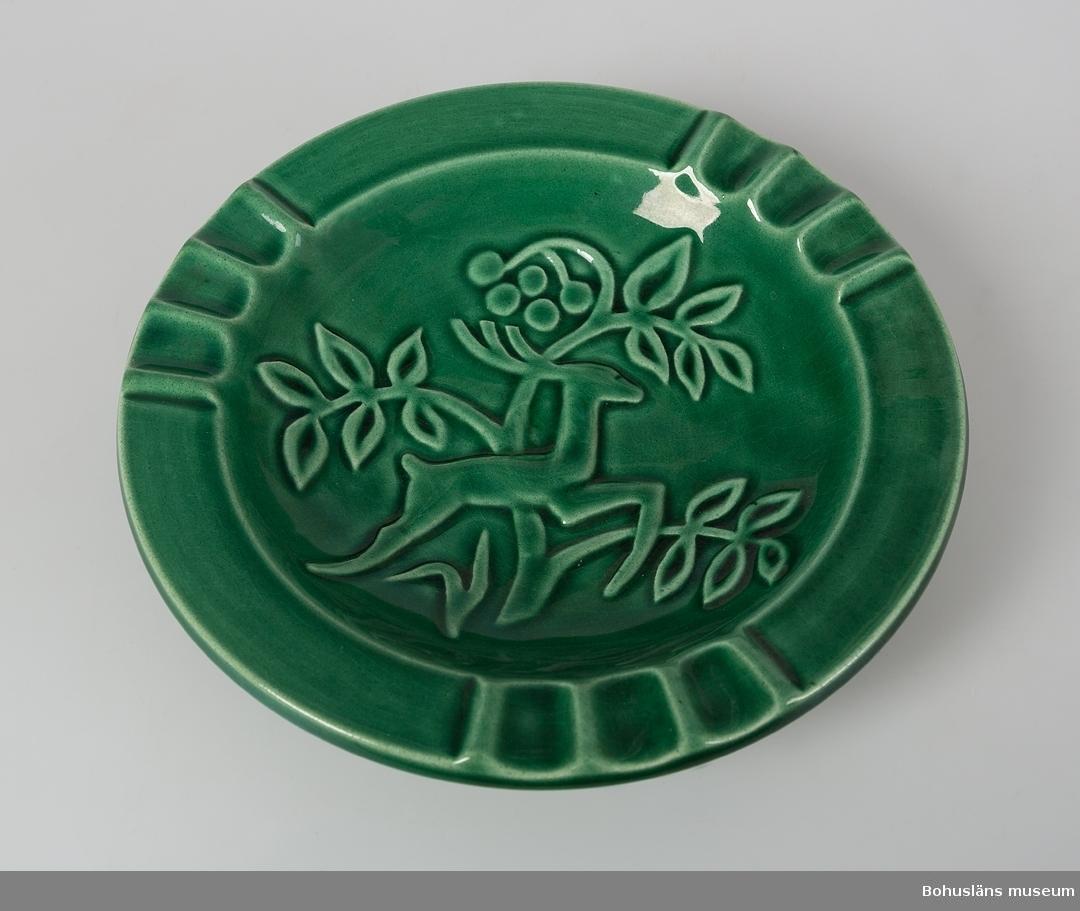 """Askfat med reliefdekor med hjort och träd. Grönglaserad. Troligen 1940-50-talen. Märkt med stämpelsignatur i blått på undersidan : """"SYCO Made in Sweden 1882-GZ."""" Tre små naggar i kanten."""