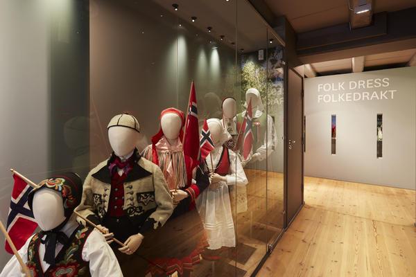 Utstillingsmonter med nasjonaldrakter og norske flagg