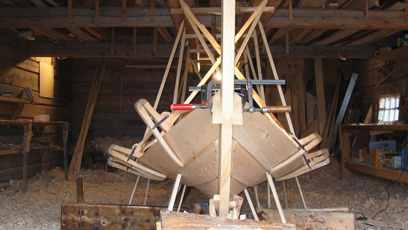 Clamps are used for holding the new strake in place before it is properly fastened. The sticks pointing down from the ceiling and up from the ground are used to shape the boat, by applying more or less pressure in different areas. (Foto/Photo)