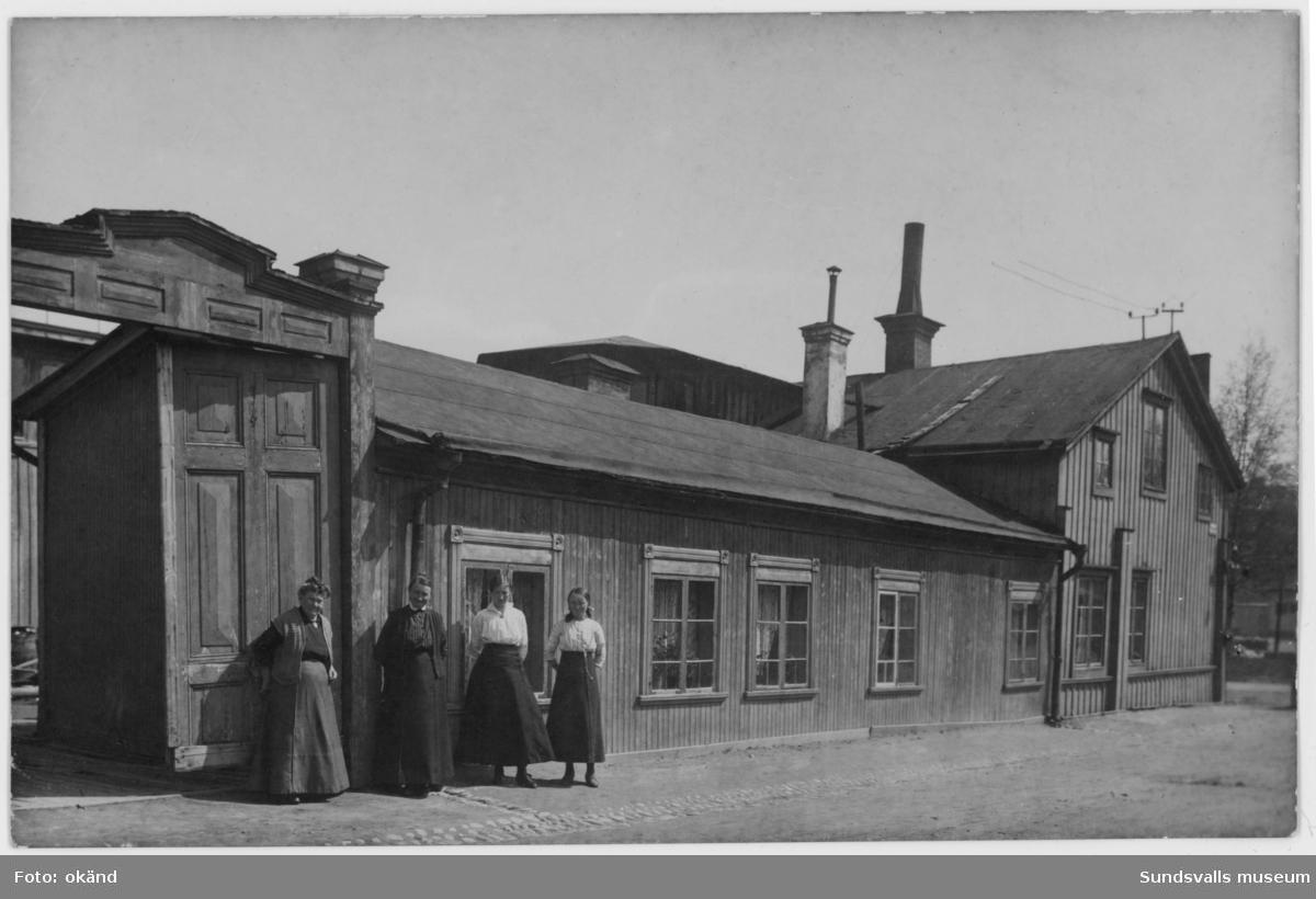 Stadsbarnmorskan Anna Hydén med två av döttrarna framför bostaden på Skepparegatan 12, Norrmalm. Bilden är tagen i hörnet Malmskillnadsgatan-Skepparegatan. Damen till vänster är troligen en granne. På samma adress finns även maken Gustaf Hydéns möbelsnickeri.