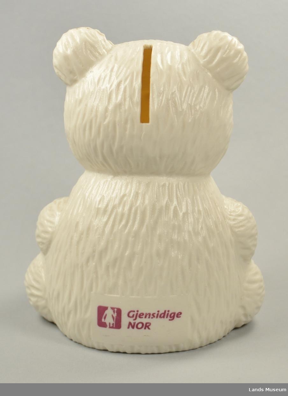 Bøssa er forma ein kvit bamse med ei blå sløyfe i halsen.
